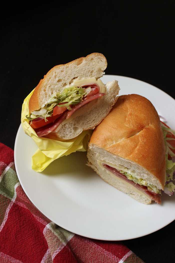 italian sub cut in half on plate