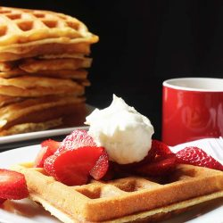 stack of waffles next to a plate with a waffle berries and cream