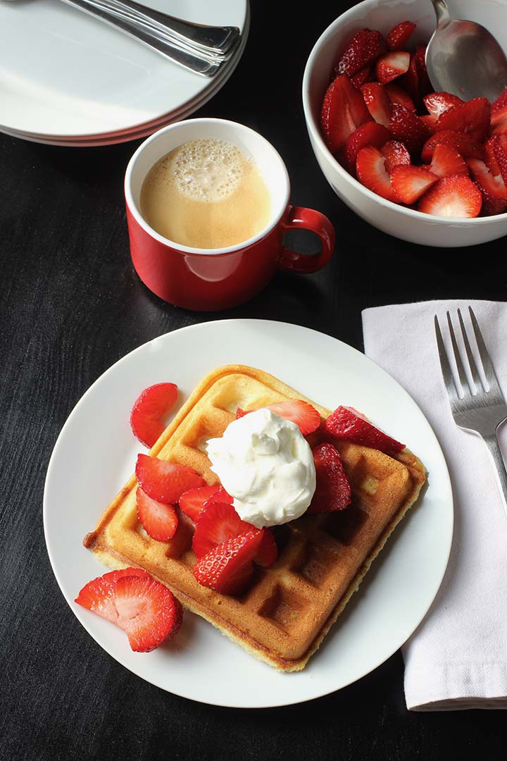 waffle on plate with cup of coffee and berries in bowl