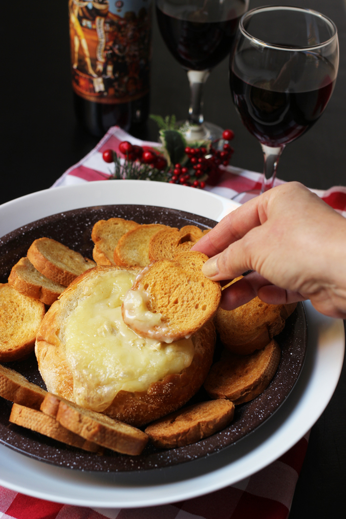 dipping bread into melted brie