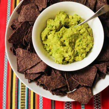 bowl of guacamole surrounded by blue corn tortillas