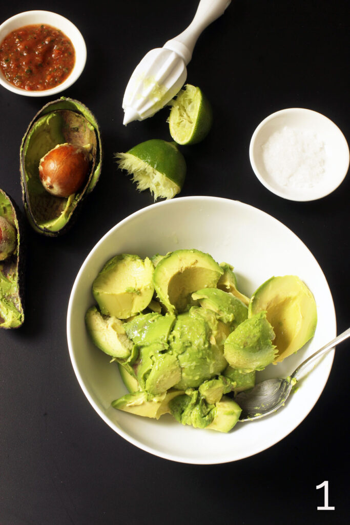 avocado scooped into bowl and lime juiced over the avocado chunks