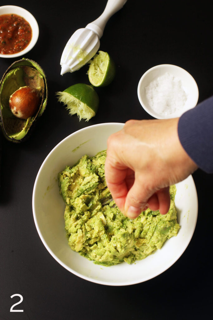 adding salt to mashed avocado in bowl