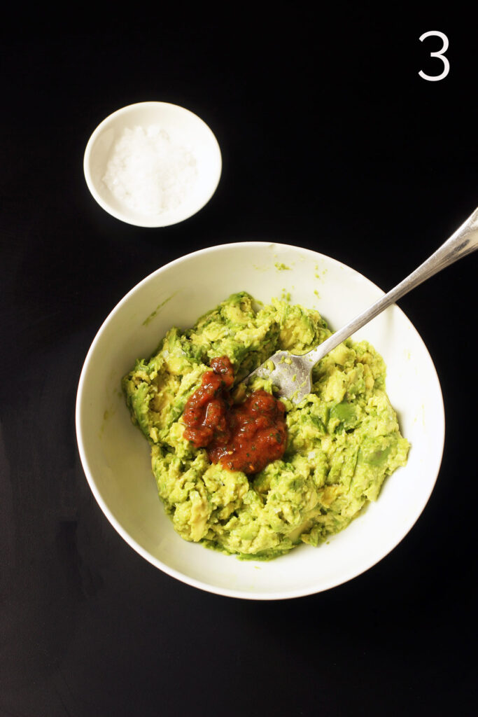 adding salsa to mashed avocado in bowl