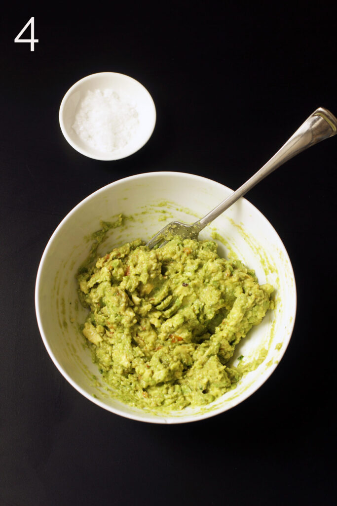 adjusting seasoning and texture of guacamole with fork
