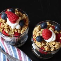 two cups of yogurt with berries and granola