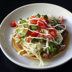 bean tostada on a white plate