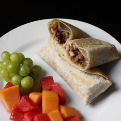 A plate of Chimichangas and fresh fruit