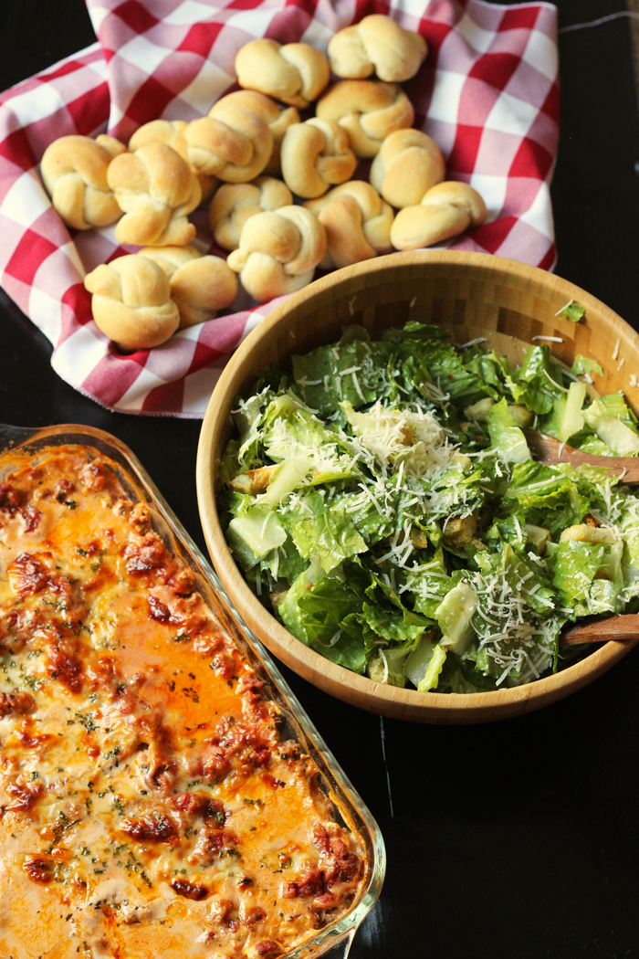 garlic knots, lasagna, and caesar salad in a bowl