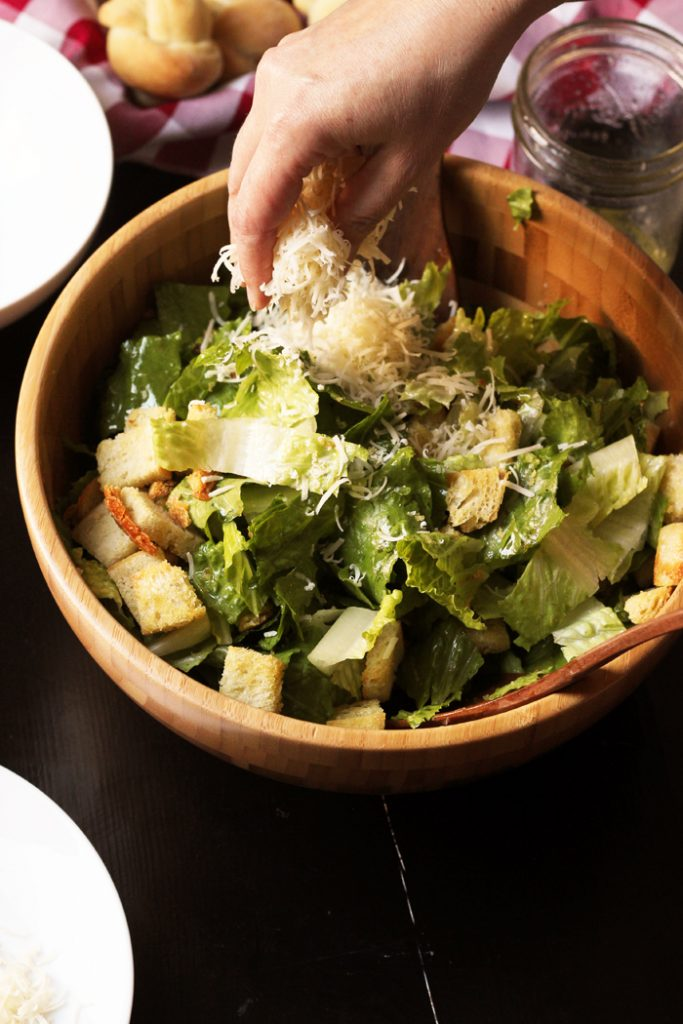 cheese being sprinkled onto a caesar salad