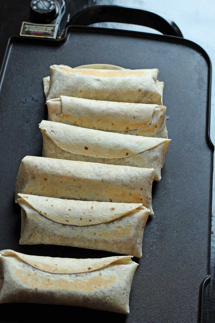 chimichangas cooking on a griddle