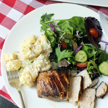 forkful of potato salad on plate with pork chop and salad