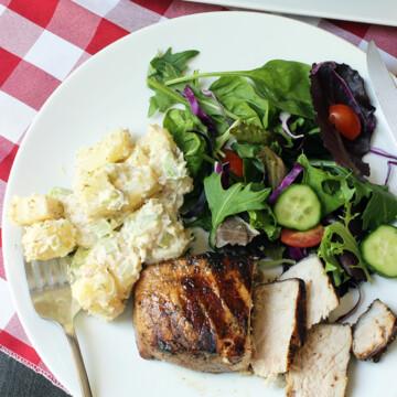 forkful of potato salad on plate with pork chop and salad
