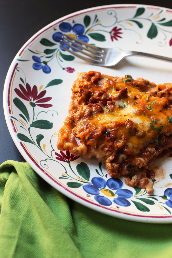 piece of lasagna on flowered plate with green napkin