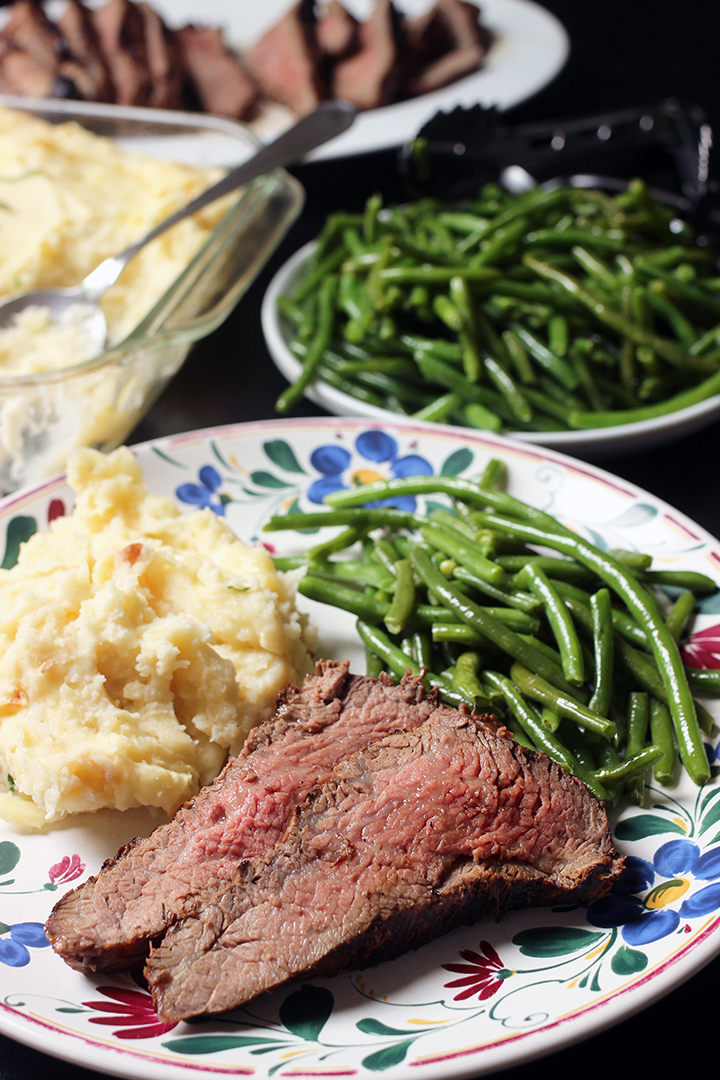 rare steak on dinner plate with potatoes and green beans