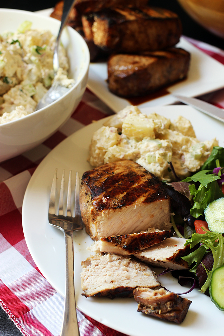 sliced pork chop on plate with fork and side dishes