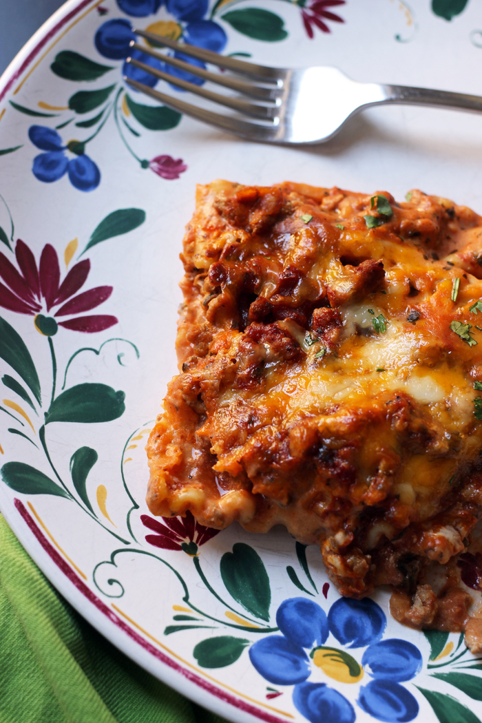 square of lasagna on plate with fork