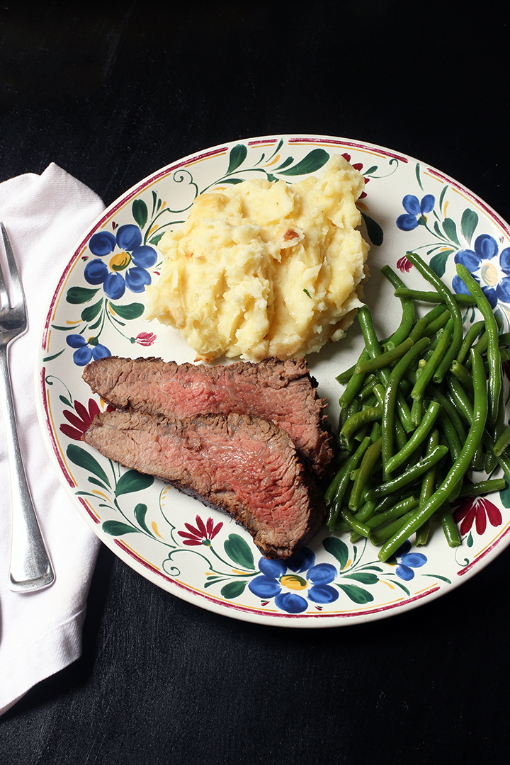 steak dinner on a flowered plate