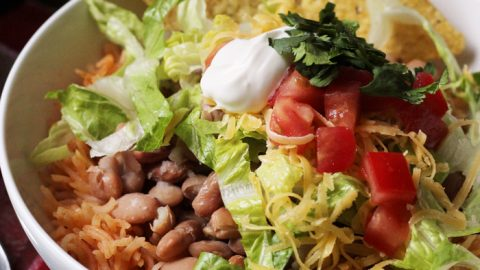 bean and rice bowl with chips and toppings