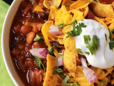 bowl of chili with toppings and fritos