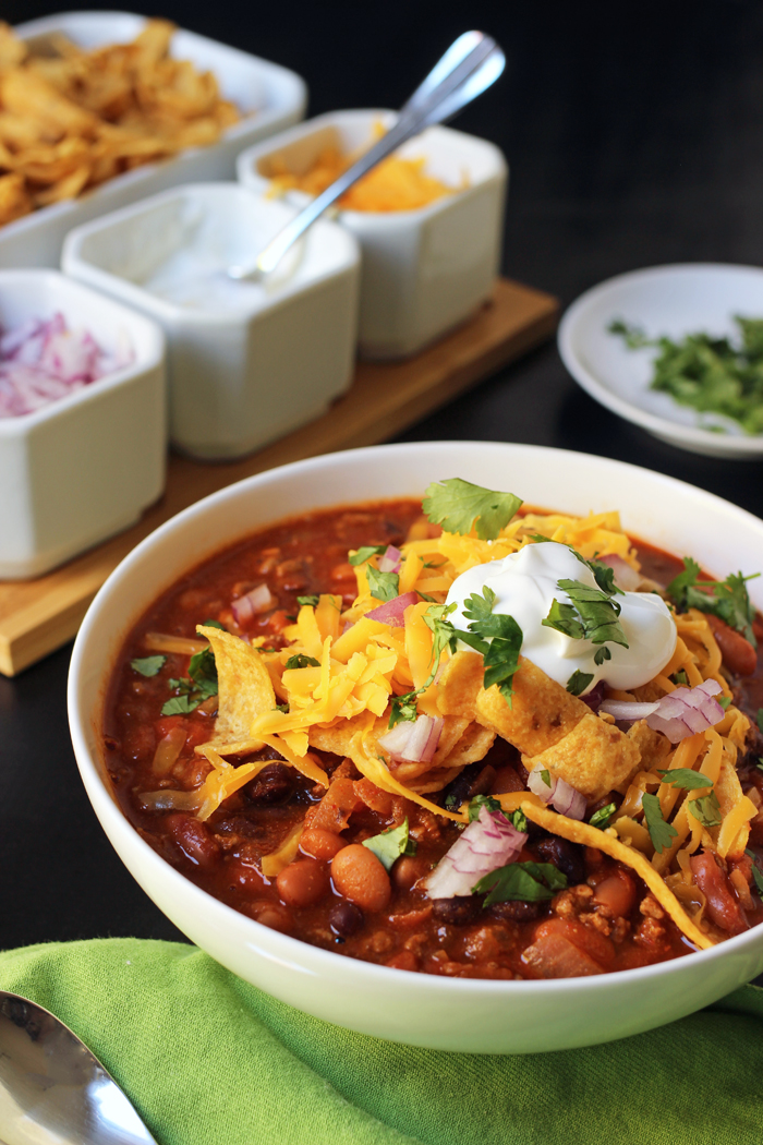 bowl of chili with toppings on side