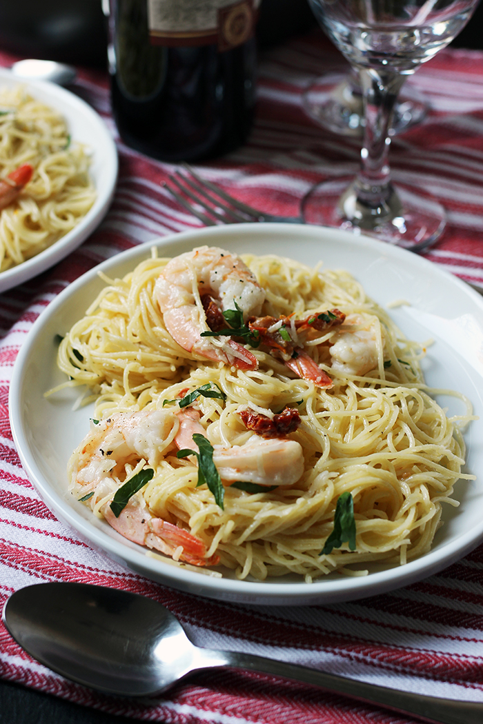 plate of shrimp pasta with glass and bottle of wine