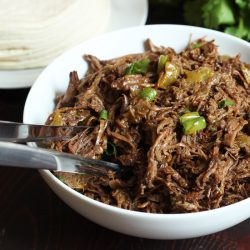 A bowl of shredded beef with tongs