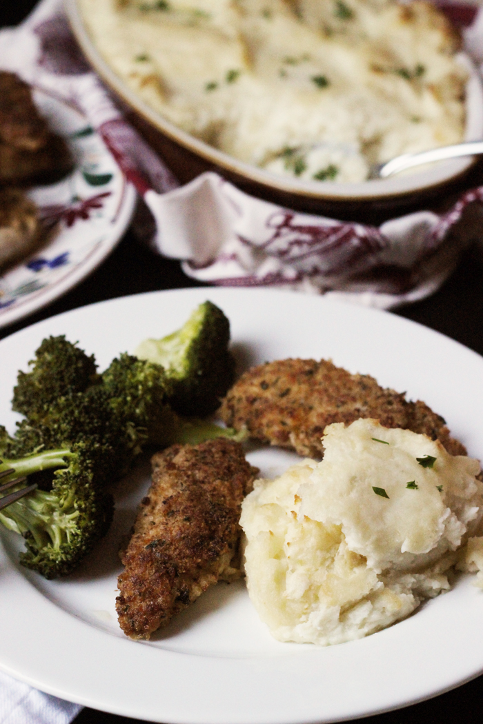 white plate with two fried chicken strips, broccoli, and mashed potatoes