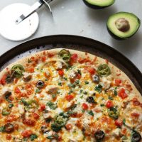 A pizza sitting on top of a pan on a table, with avocado
