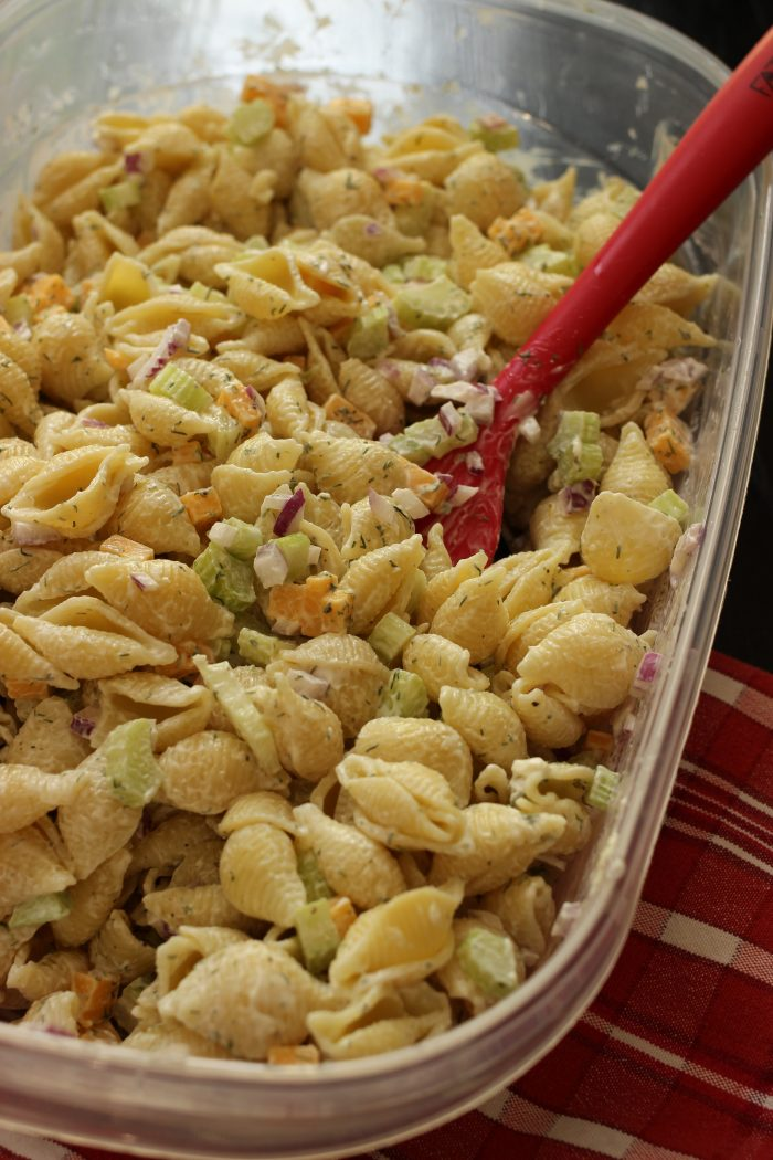 dish full of macaroni salad with red spoon