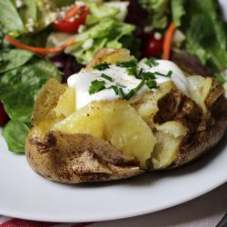 A plate of salad and baked potato with toppings