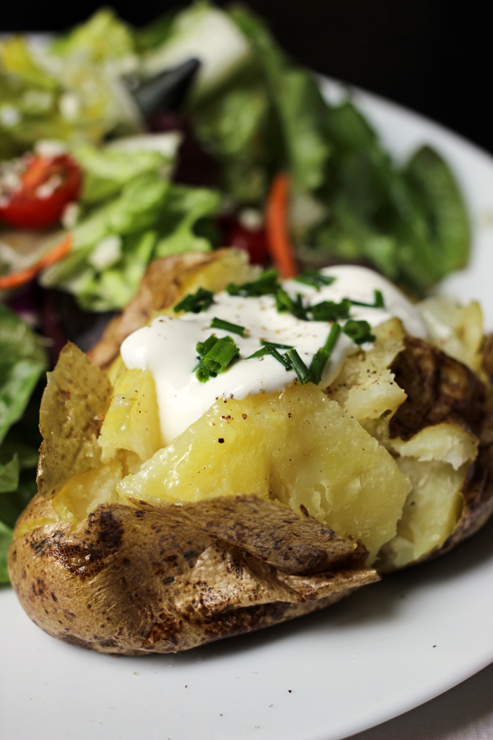baked potato with toppings on plate with salad