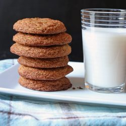 Snickerdoodles stacked next to glass of milk