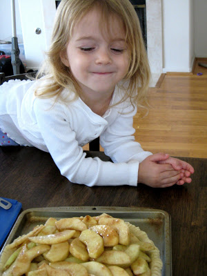 A little girl sitting at a table with food, with Apple pie