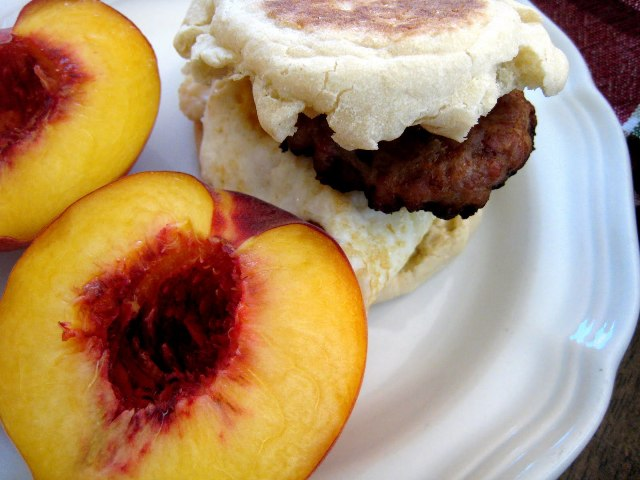 A close up of breakfast sandwich on a plate, with nectarine
