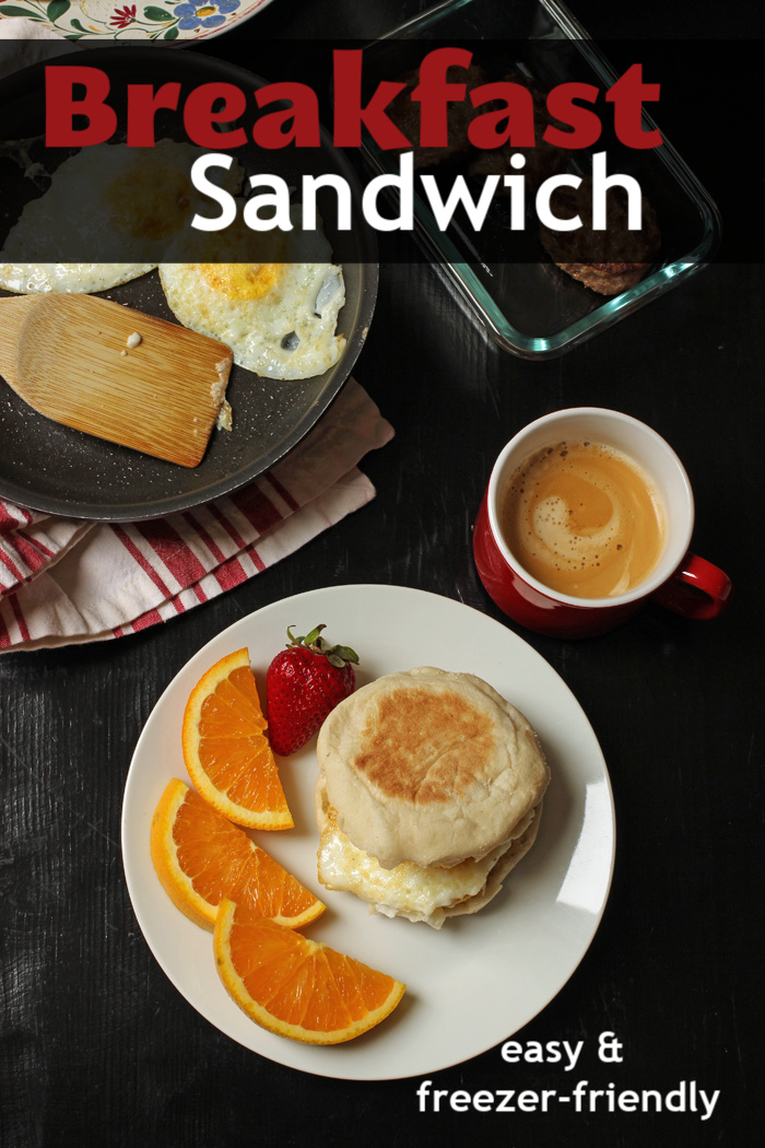 breakfast sandwich on plate with fruit and coffee