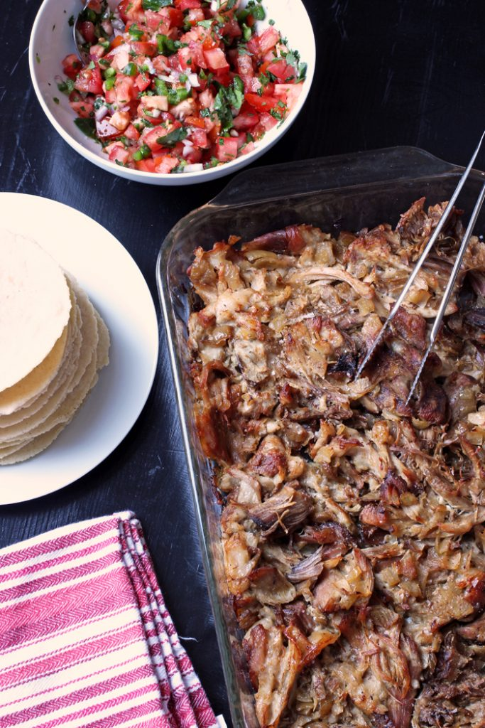 carnitas in glass dish next to stack of tortillas and bowl of salsa