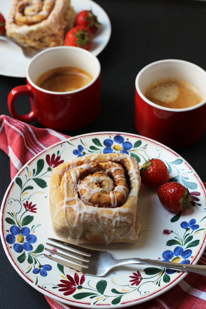 cinnamon roll on flowered plate with strawberries and coffee cups