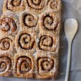 dozen cinnamon rolls on parchment paper with glazing