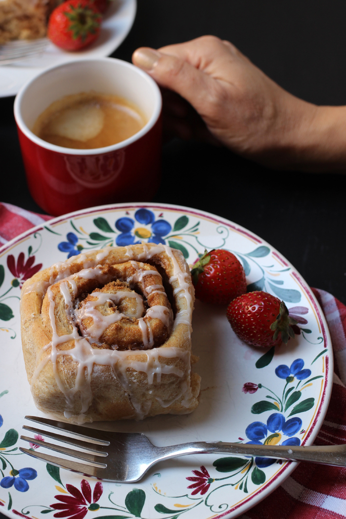 flowered plate with cinnamon roll and strawberries hand on mug