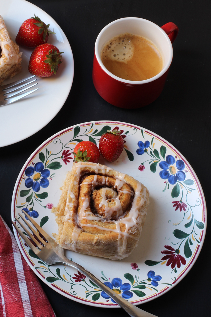 flowered plate with cinnamon roll and strawberries with red coffee cup