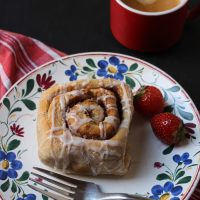 cinnamon roll and strawberries on a plate