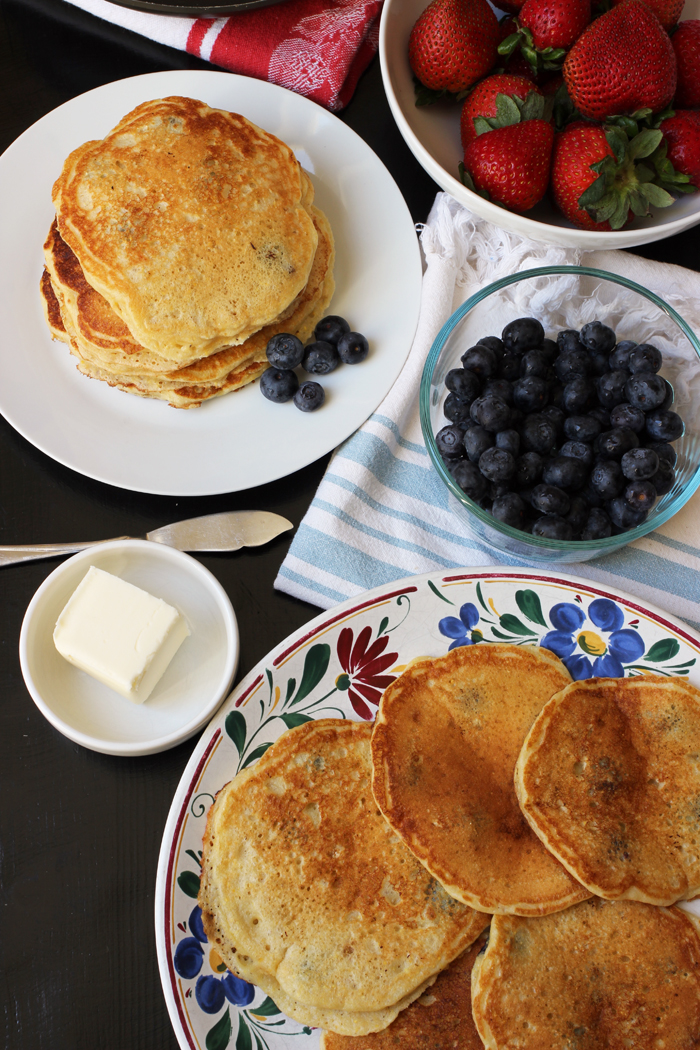 breakfast table laden with pancakes berries and butter