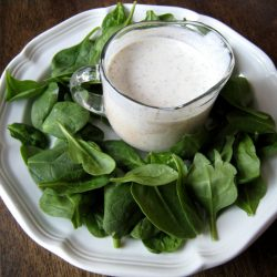 pitcher of dressing surrounded by baby spinach