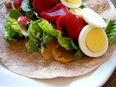 A close up of an open wrap with hummus and veggies