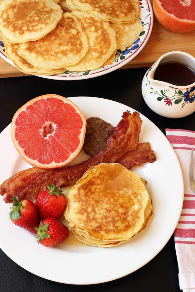 breakfast plate with pancakes fruit and meat
