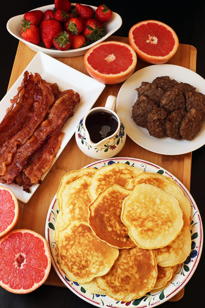 overhead shot of breakfast table with pancakes fruit sausage and bacon