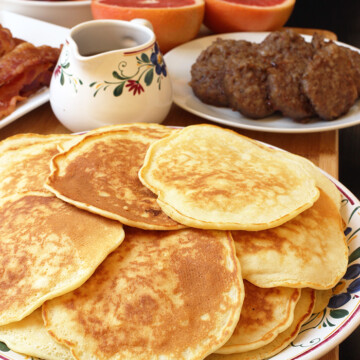 plate of pancakes on breakfast table with other breakfast foods