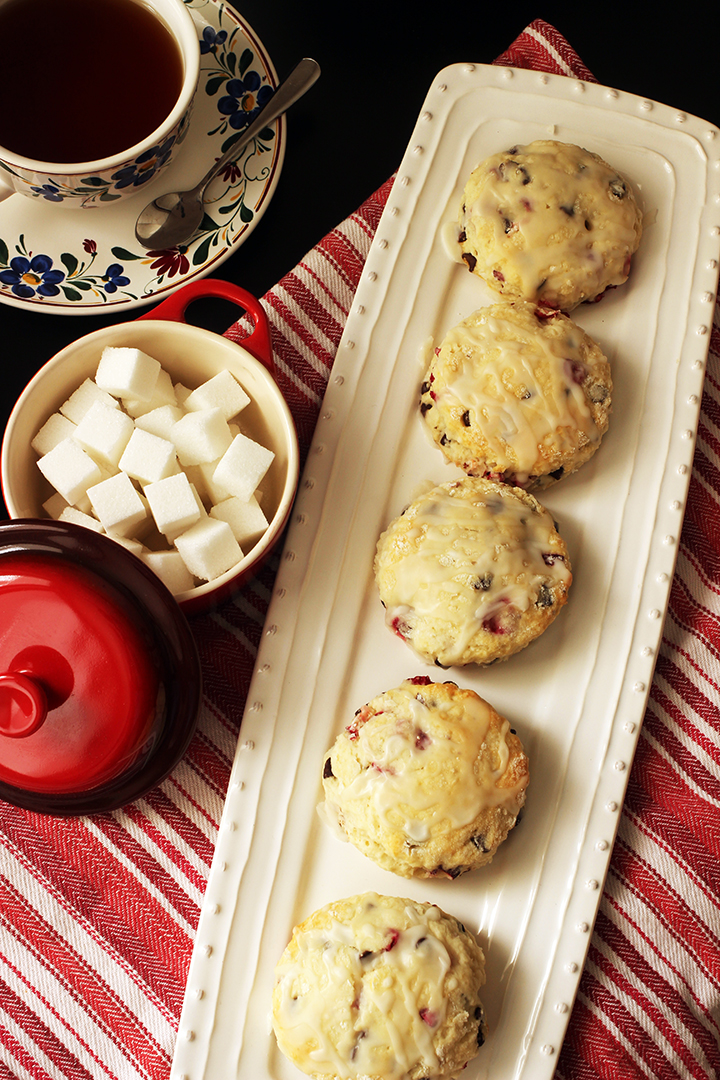 tea cup and sugar bowl next to tray of cranberry scones