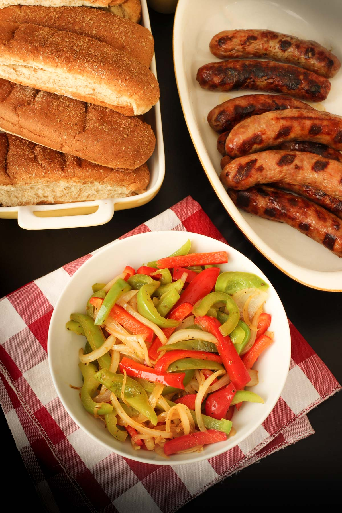 bowl of sauteed peppers and onions on buffet table with hot dog buns and brats.